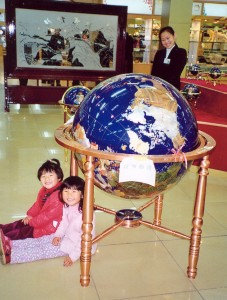 Cecilie and Yanmei sit and wait under the globe