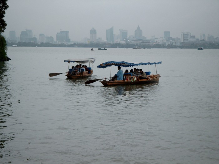 Row boats on the West Lake with the Hangzhou skyline in the background